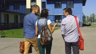 Cheerful three students are chatting in campus
