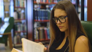 Clever young woman sits on armchair and reads book at the library