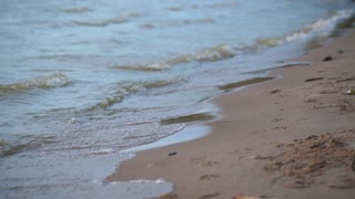 Close up of surf with soft sea waves rushing on sandy beach on sunset with sun reflection
