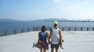 couple in love with skateboards on the promenade down the stairs