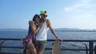 couple in love with skateboards standing on the promenade and laugh
