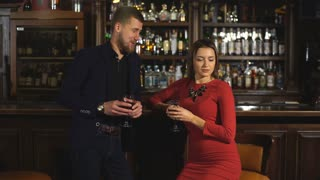 Cute couple talking and having a drink in a bar