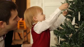 Cute little girl is  decorating the christmas tree