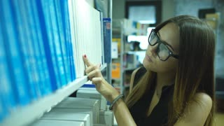 education and school concept - happy student girl or young woman with book in library