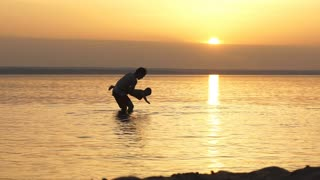 Father and Son Playing on the Beach at Sunset