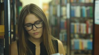 female student read book in library with bookshelf as background