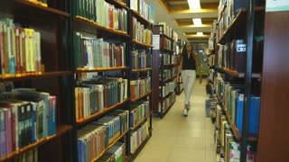 Female student walking in the library at the universit