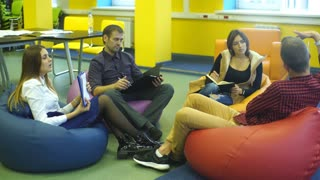 four students talking in class