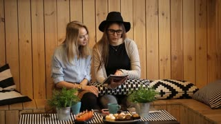 friendship and happiness concept - two girls reading magazine