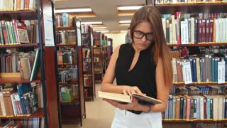 girl reading a book standing in the library