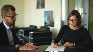 Good looking young businessman closing a deal with a female client while she signs a contract
