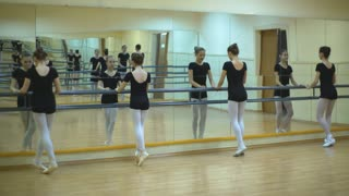 group of four young ballerinas standing in row and practicing ballet