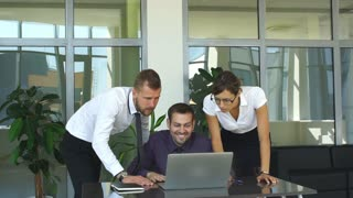 Group of happy business people in smart casual wear looking at the laptop and gesturing