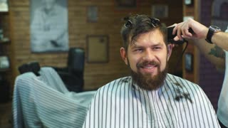 Hairdresser makes hairstyle a man with a beard