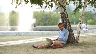 Handsome hipster using laptop in park on a summers day