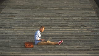Handsome student sitting on stone steps and using a laptop