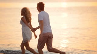 happy couple is running along the shore at sunrise
