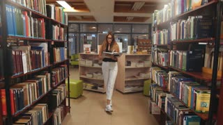 happy student girl or young woman with book walking in library