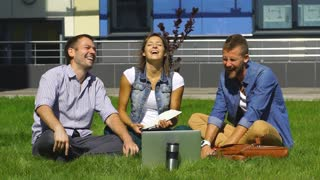 happy students sitting on the lawn and laugh