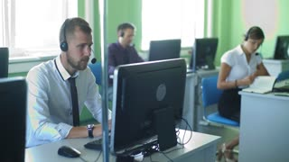 Male call centre worker, looking at screen