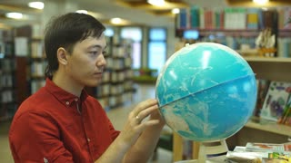 male college student looking at a globe