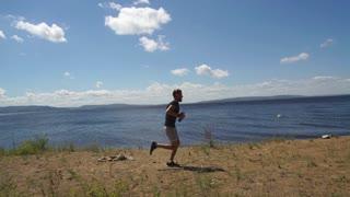 male runner runs along the river