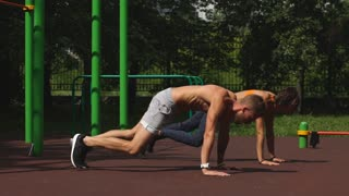 Man and woman exercising at the city park. Beautiful young multiracial couple