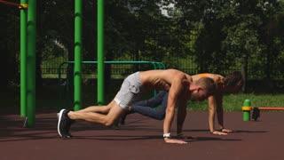 Man and woman exercising at the city park. Beautiful young multiracial couple