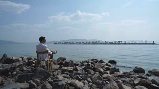 man in a white jacket sitting on a chair on the riverbank and enjoying the view