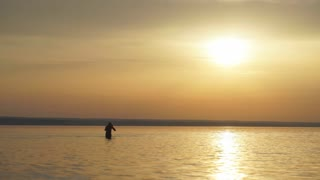 Man in Water on a sea in a sunrise