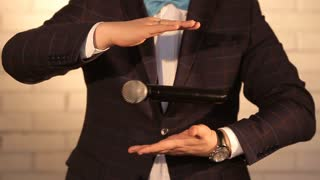 man magically turns the microphone in the air