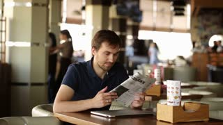 man reading the newspaper and working at a laptop