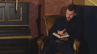 man sitting in a chair and reading a book