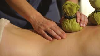 Masseuse doing Thai massage with salt bags