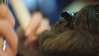 Master cuts hair and beard of men in the barbershop, hairdresser makes hairstyle for a young man.