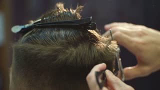 Master cuts hair and beard of men in the barbershop, hairdresser makes hairstyle for a young man
