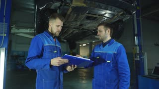 Mechanic And Trainee Working Under Car