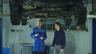 mechanic with clipboard talking to man or owner at car shop