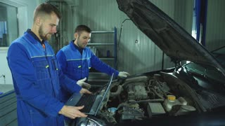 mechanics with laptop in auto repair shop