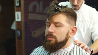 Men's hairstyling, haircutting, in a barber shop or hair salon.