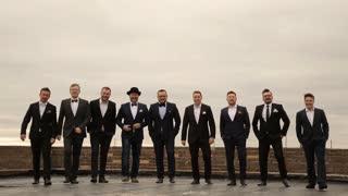 nine handsome men in suits having fun