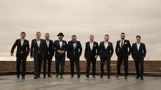 nine men in suits having fun