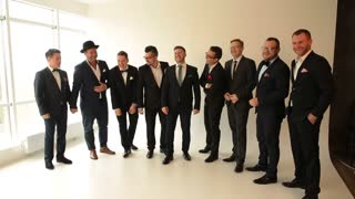 nine men in suits posing for the camera