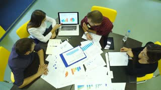 people, statistics and team work concept - close up of creative team sitting at table and pointing finger to paper wit