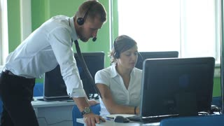 Phone operator works in an office call center, helping his colleague.