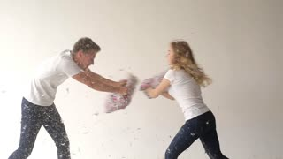 Pretty couple fighting pillows