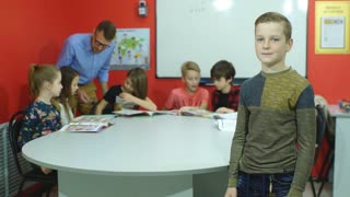 Redhead schoolboy stands near a school board smiling