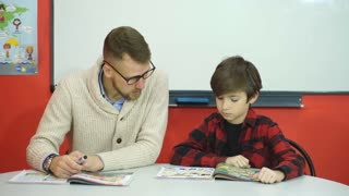Schoolboy Studying In Classroom With Teacher