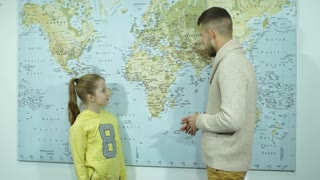 schoolgirl showing countries on a map of the teacher