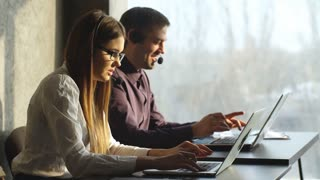 Side view of beautiful young business woman and handsome businessman in headsets using laptops while working in office.